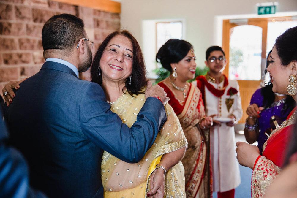 Brides family hugging in farm reception