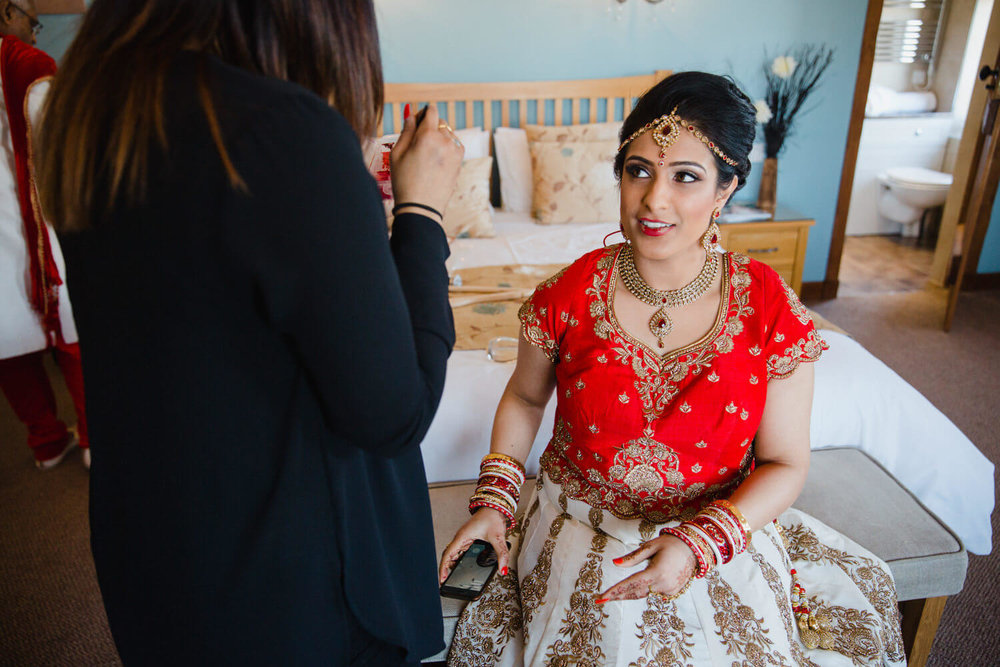 Bride sitting on bed in preparation for wedding ceremony