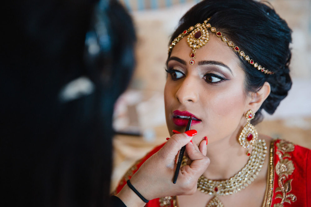 Close up photograph of bride having lipstick applied as part of make up bridal preparation