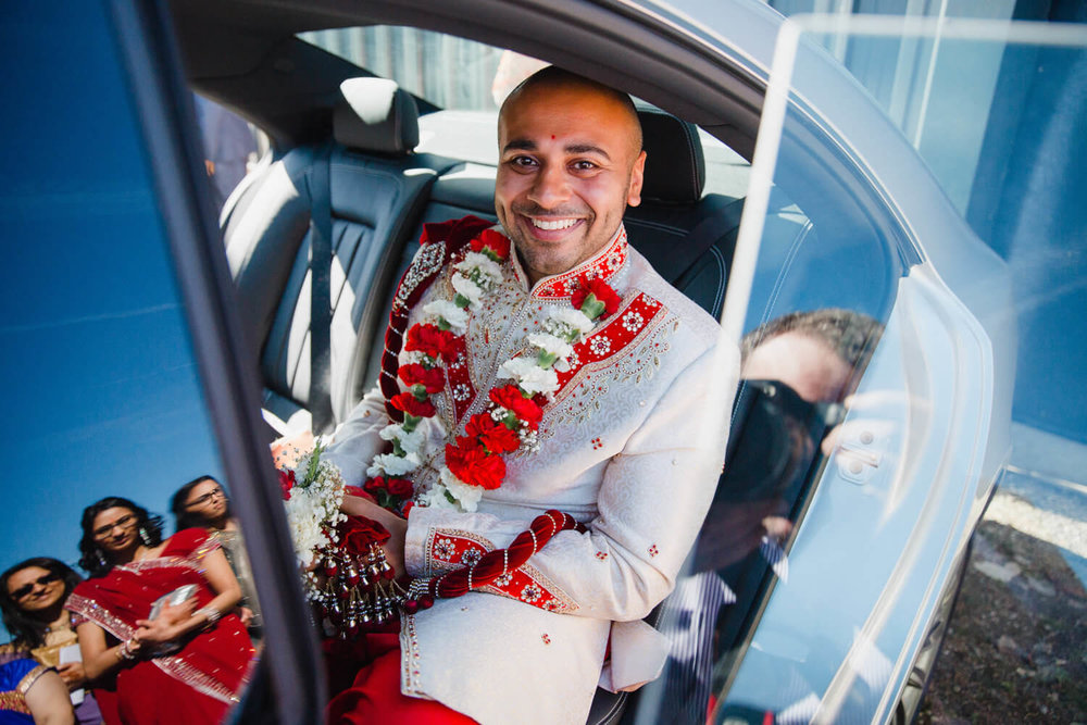 groom in car with bridesmaids in window reflection