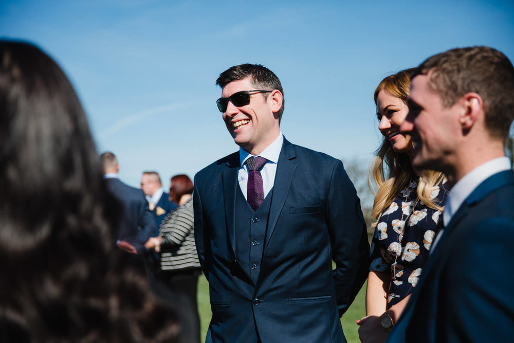 Wedding guests on field laughing at joke