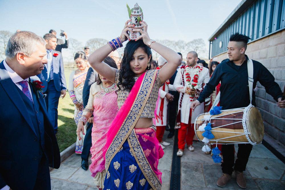 bridesmaid balancing coconut on head leading milni ceremony