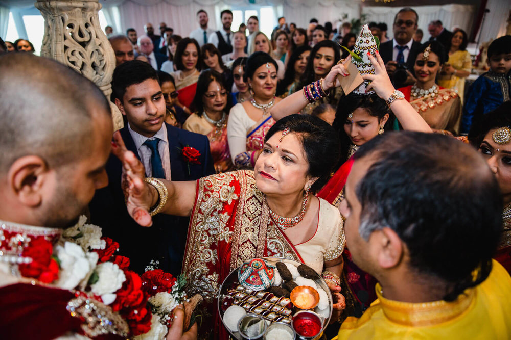 mother of groom applies sindoor powder to grooms head