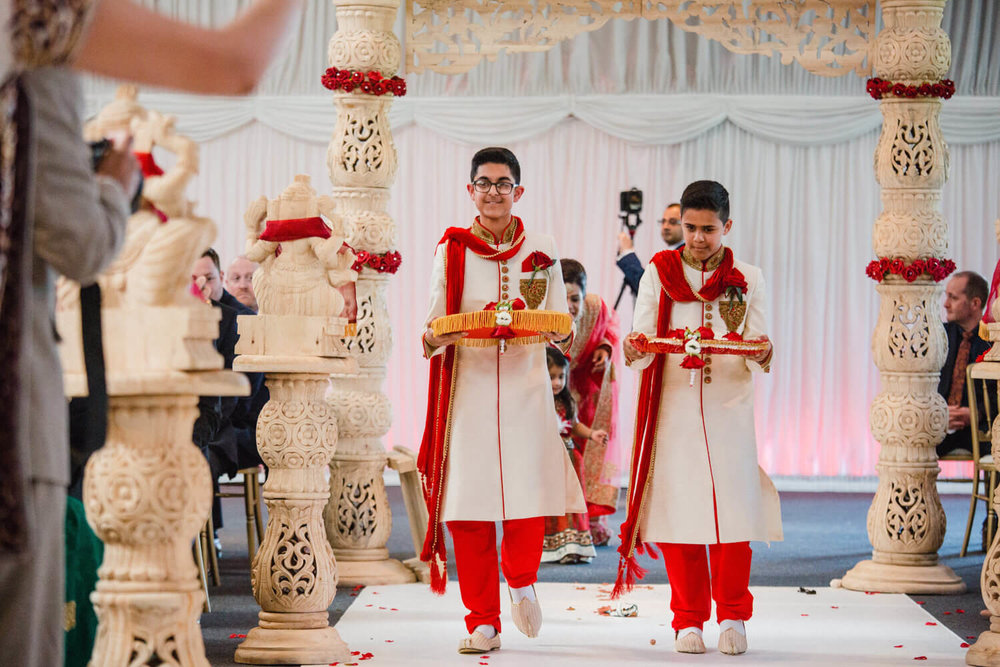 Pageboys walking down aisle together