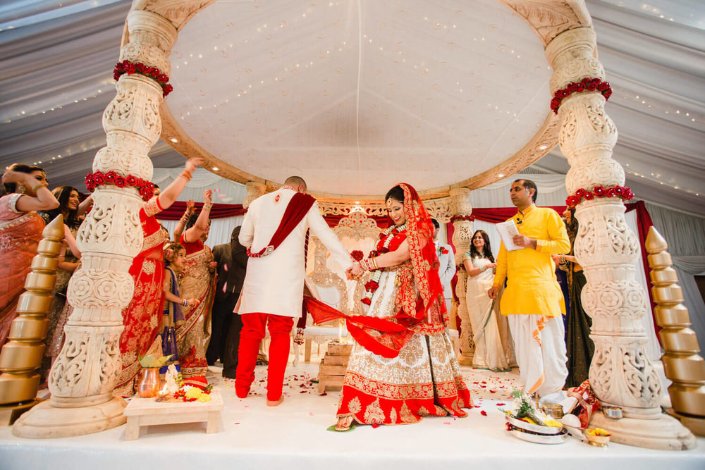 bride stands on nut as part of hindu wedding tradition