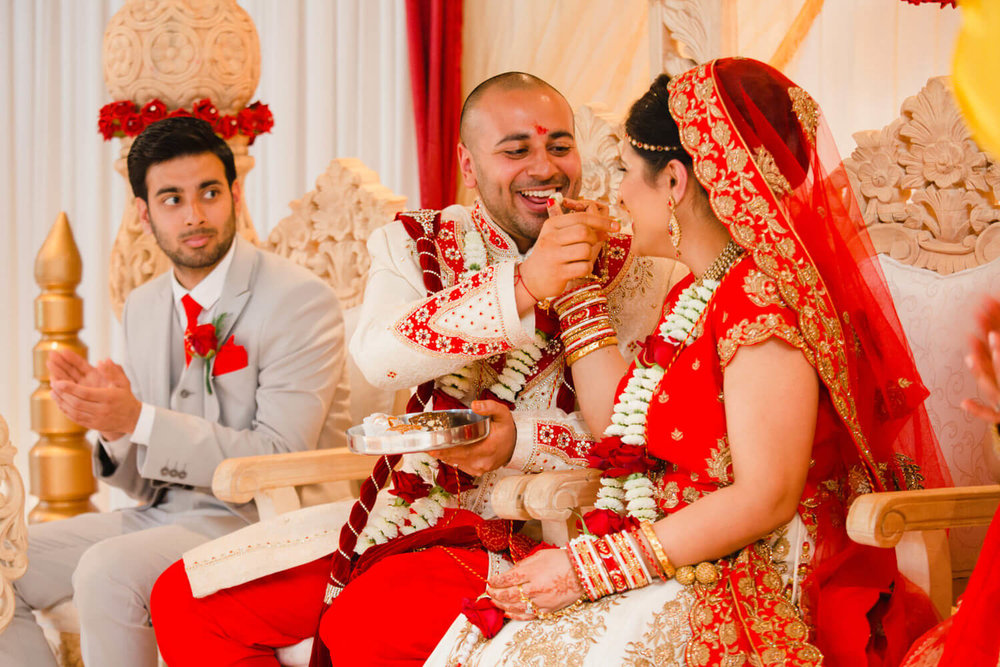 newlyweds exchanging food in front of friends and family