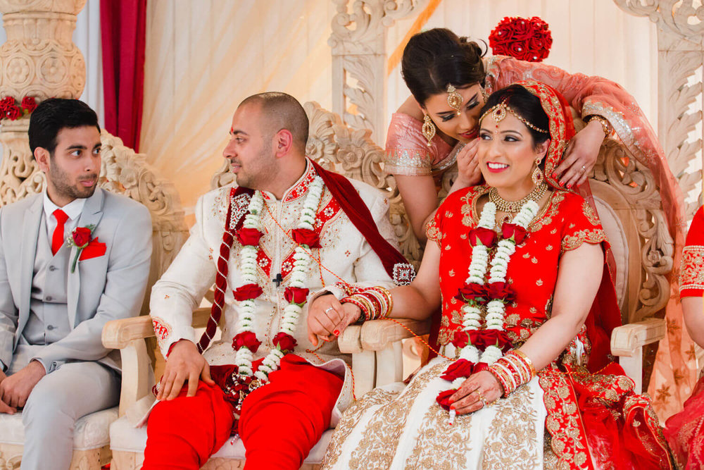 bridesmaid whispers into brides ear as hindu tradition