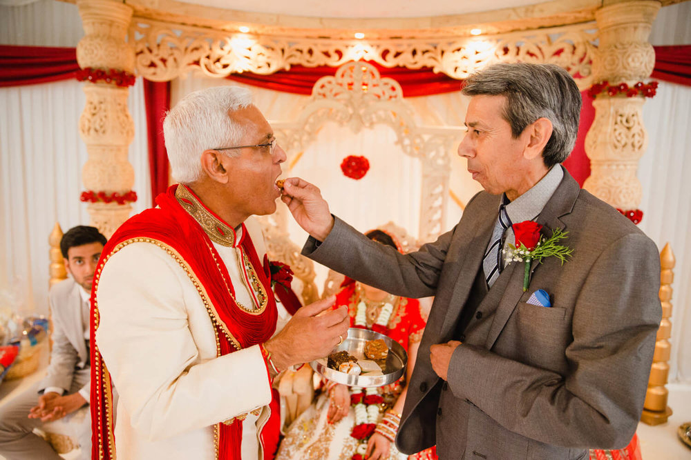 fathers of bride and groom feed each other