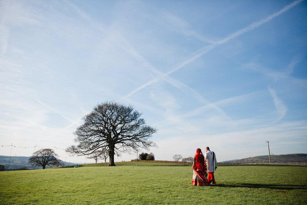 wedded couple take a walk over to oak tree