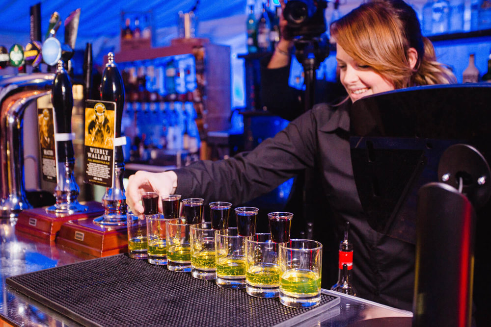 bar-maid lining up jagerbombs drinks for bridal party