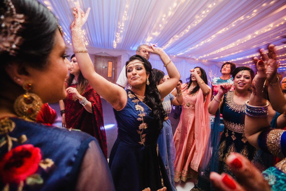 bride pointing into air while dancing with friends to music