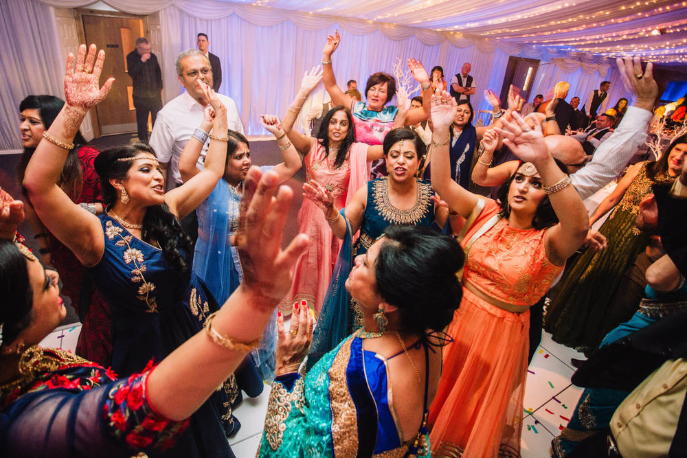 entire bridal party with their arms held high into the air dancing to wedding music