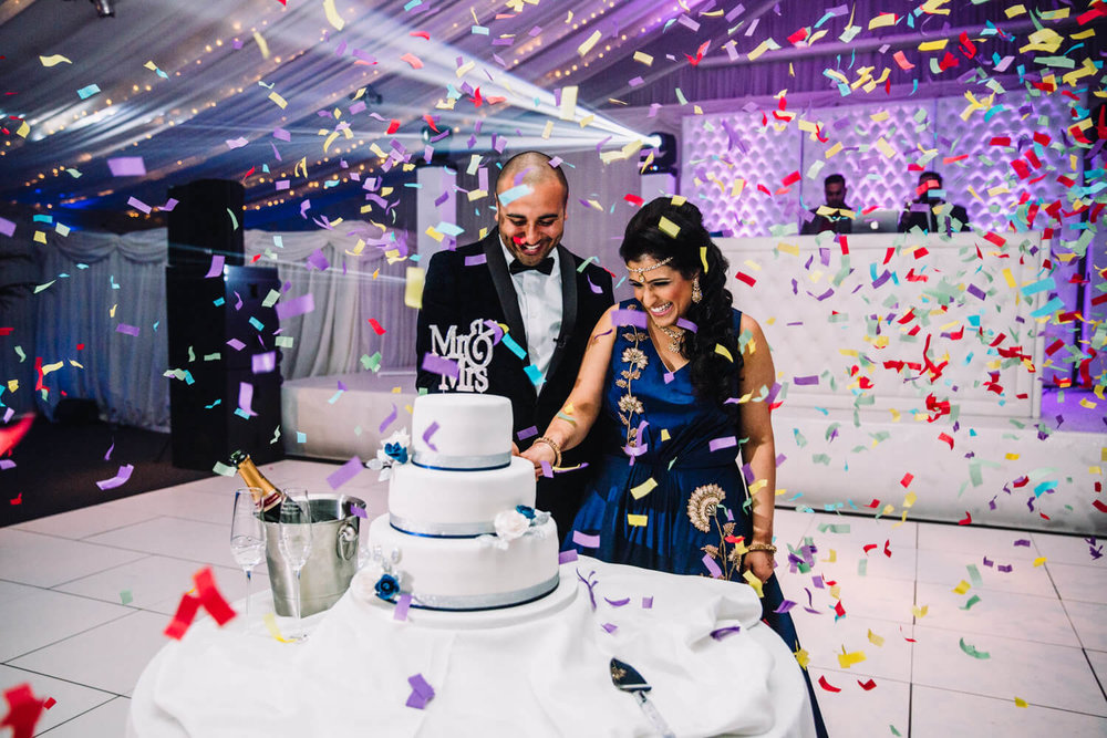 bride and groom cutting the cake underneath shower of confetti