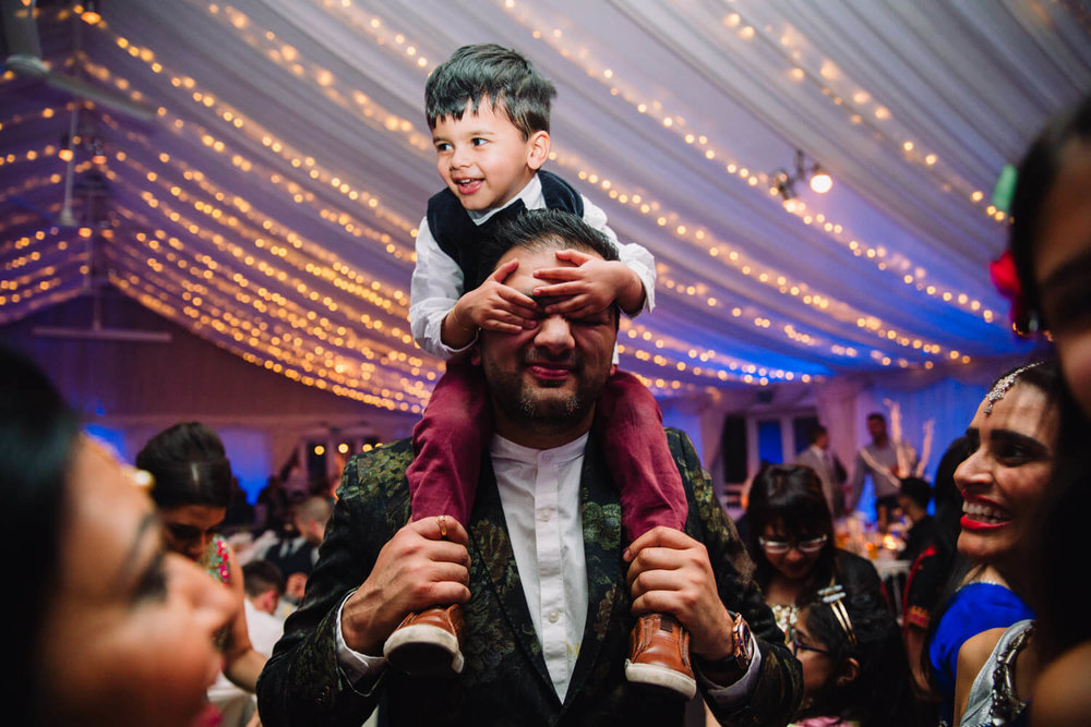 pageboy on shoulders of guest covering his eyes