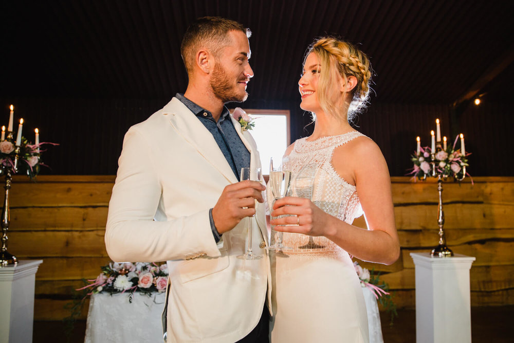 Bride and Groom clinking champagne glasses at top of aisle after ceremony