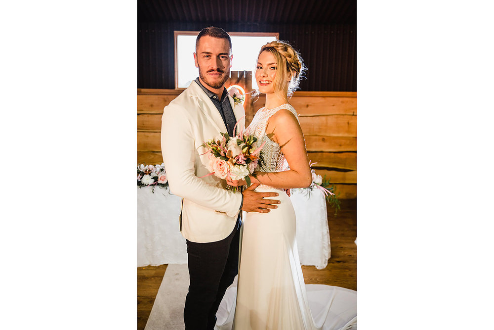portrait photograph of bride and groom celebrating wedding at farm