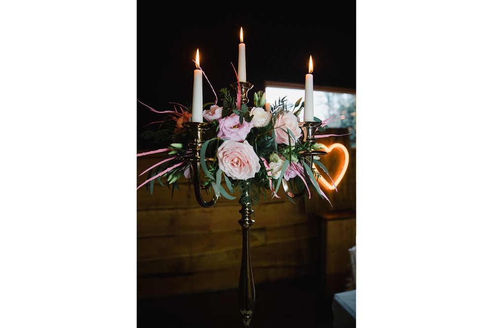 candelabra holding candles and floral bouquet