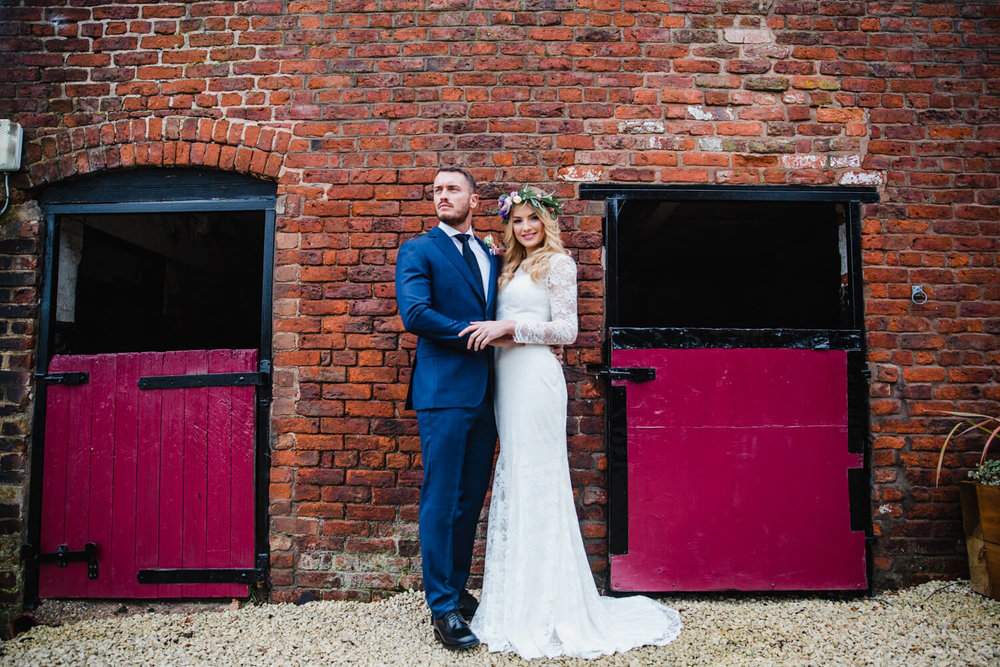 wide angle photograph of newlyweds posing in barn doors