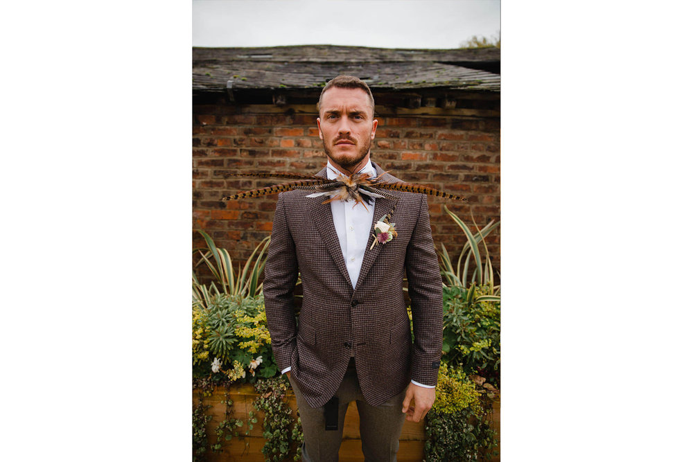 Portrait of Groom posing in front of stable wearing pheasant bow tie