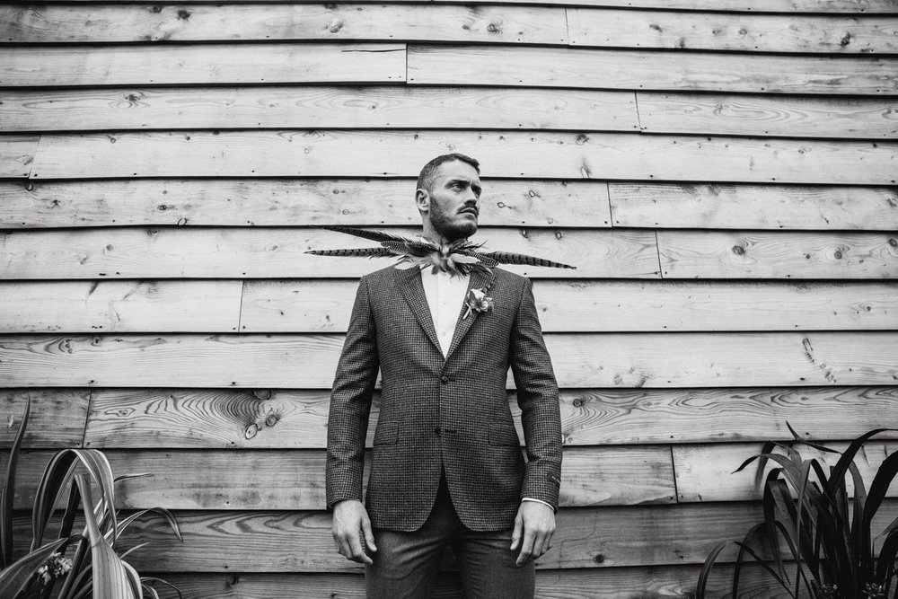 Black and White Photograph of Groom Posing in front of wooden fence