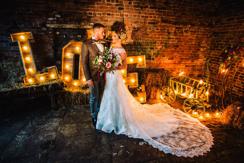 Wide angle photograph of bride and groom in front of love lettering
