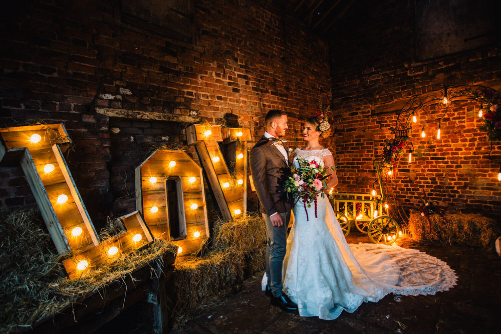 Happily married couple pose in barn lit with festoons