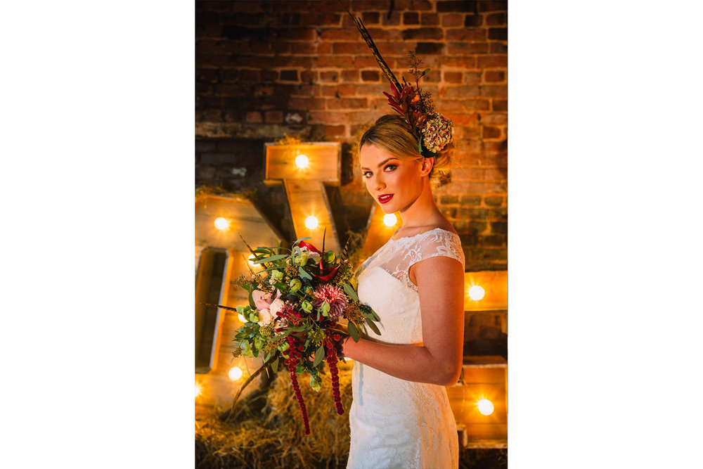 bride posing in front of light up letters