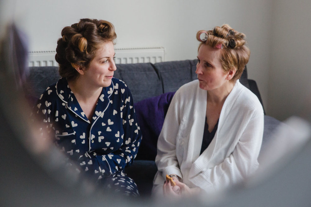 bride in pyjamas talking to mum on sofa