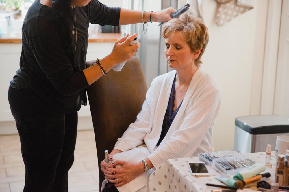 mother of bride having hair sprayed by make-up artist