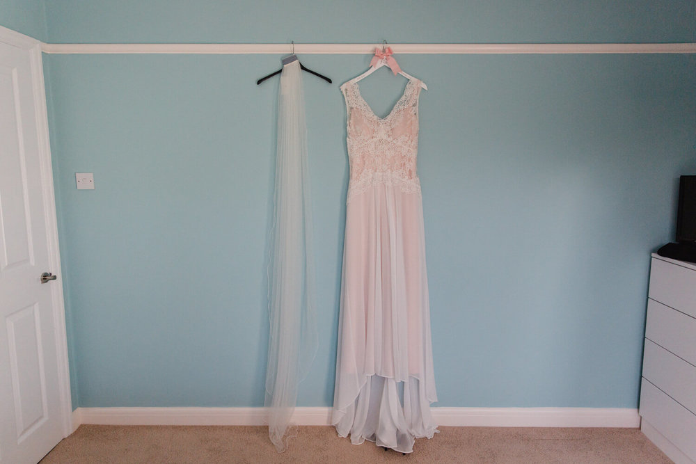 wide angle lens photograph of wedding dress and veil hung up against wall