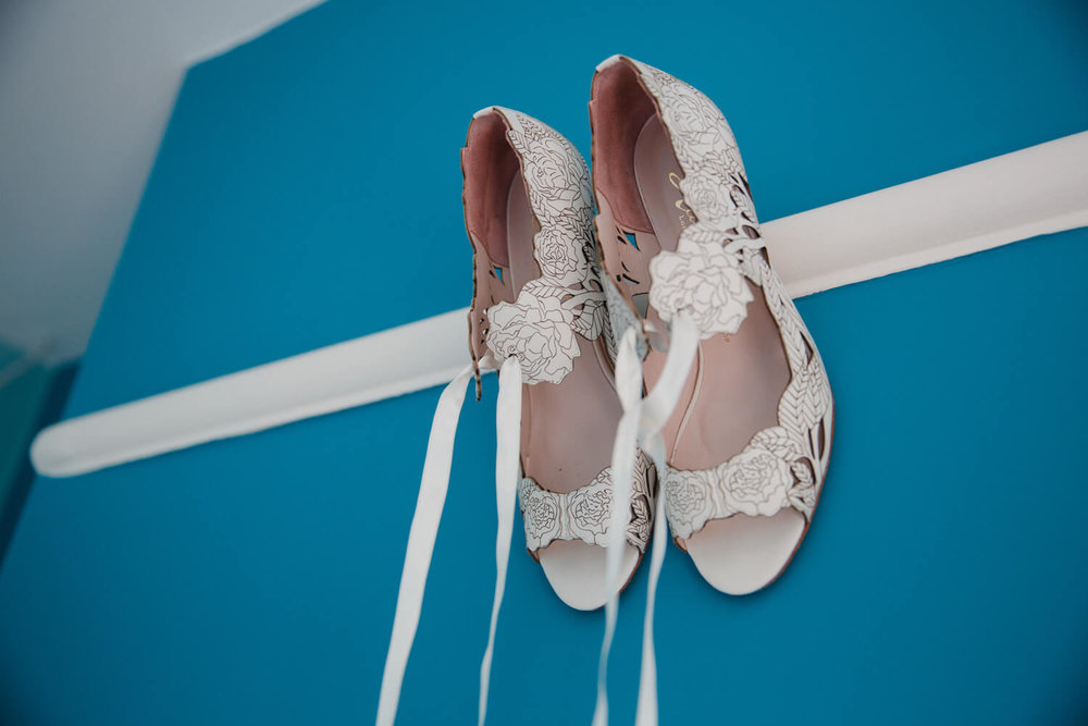 wedding shoes hung against dark blue wall