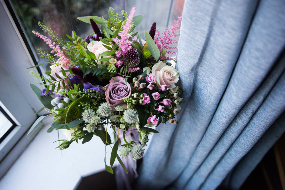 bouquet of flowers sitting against window
