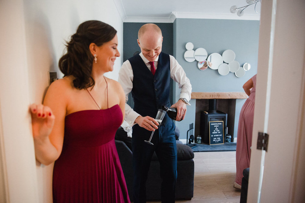 groomsman pouring glass of wine in living room