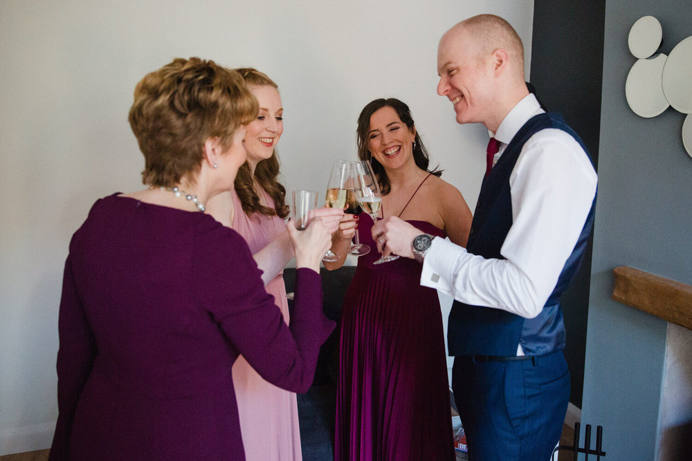 bridal party and groomsman clinking champagne flutes together and laughing