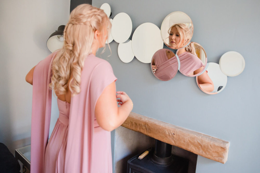 bridesmaid looking in circular mirror on wall