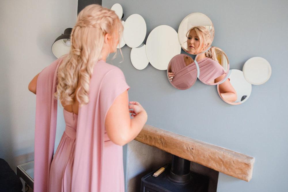 bridesmaid looking in circular mirror on wall