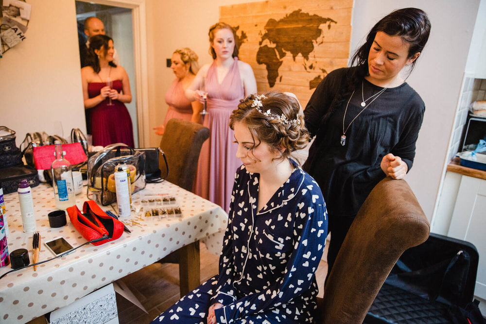 bride having make up applied in kitchen surrounded by bridal party and family