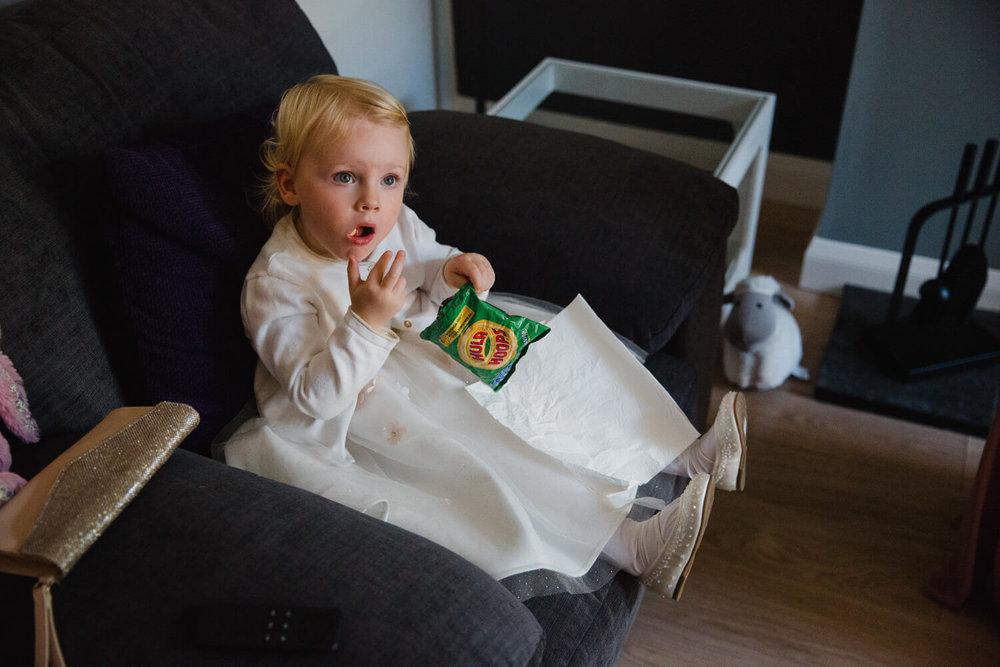 flower girl eating crisps while sat in chair