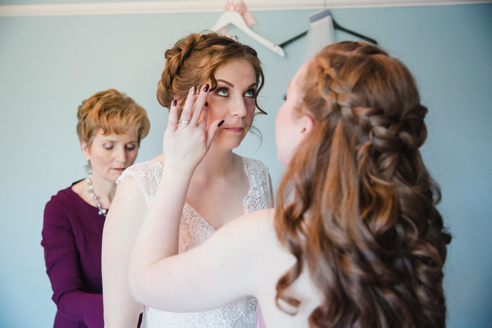 bridesmaid fixing headpiece tiara for bride