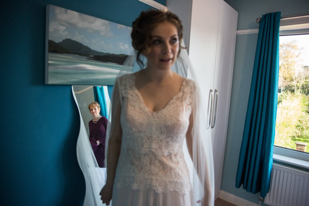 mother of bride looking on at daughter getting ready
