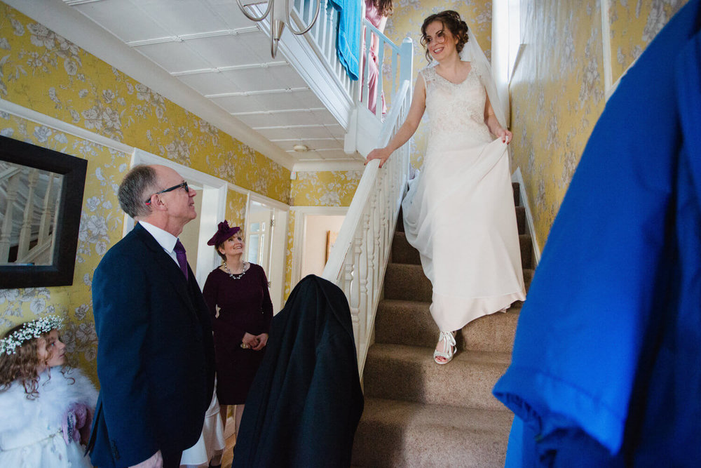 bride walking down stairs for first look and to be greeted by father