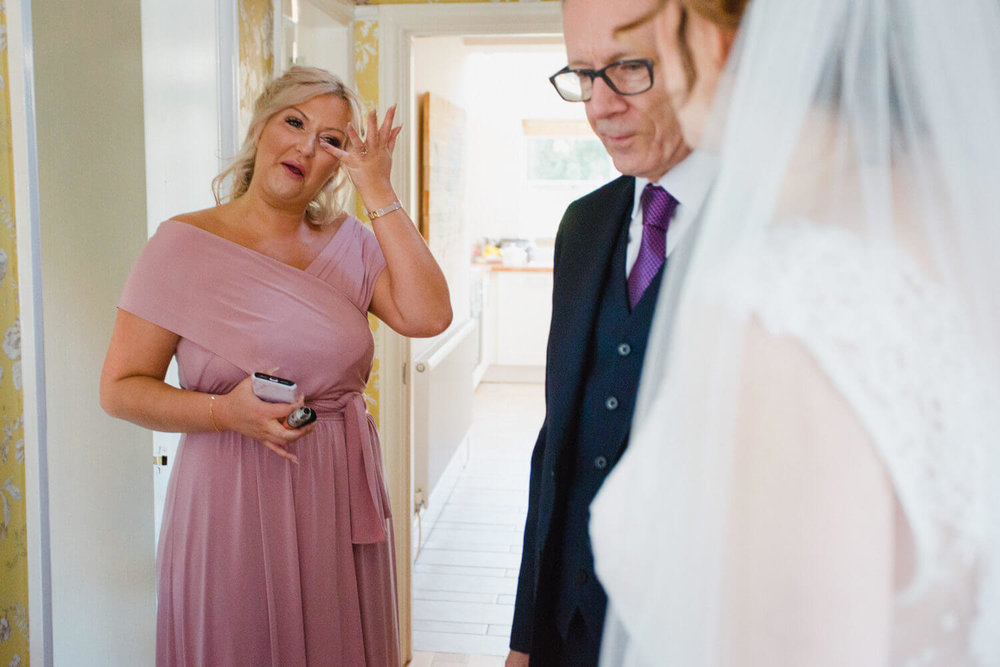 bridesmaid wiping away a tear after seeing bride
