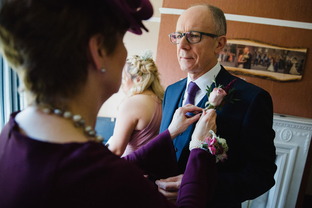 father of bride having pinhole flower attached to suit lapel