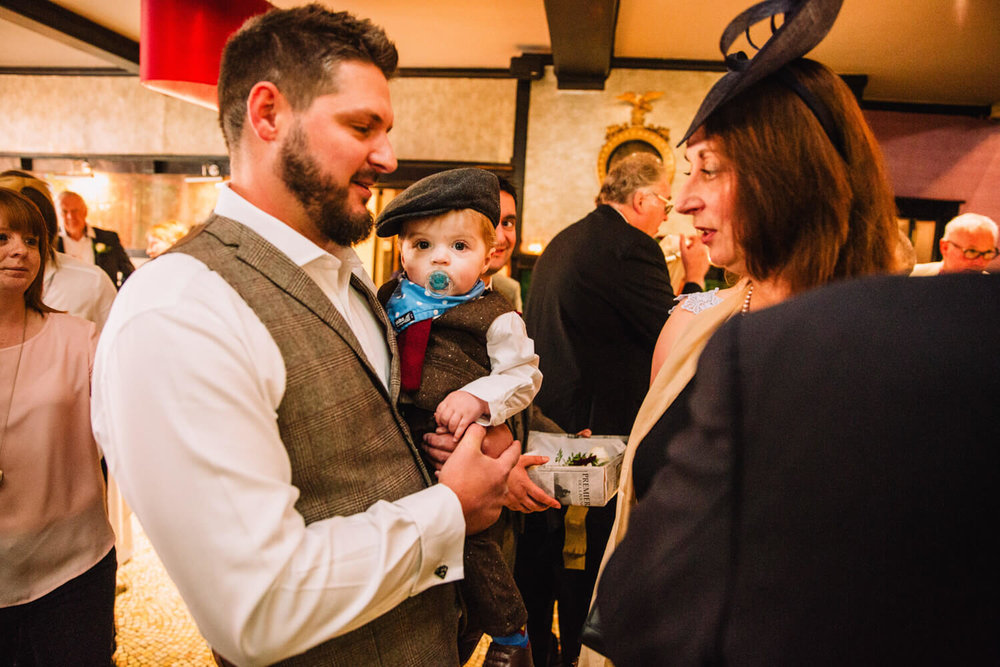 pageboy looking into camera being held by groom
