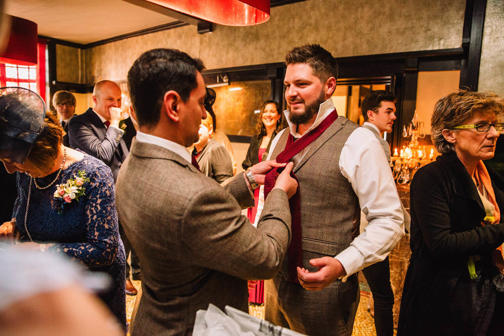 groom having bowtie tied by best man