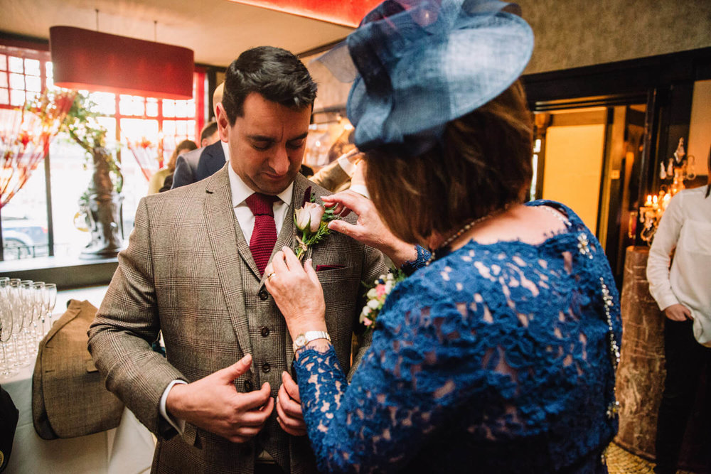 mother of groom fixing pinhole flower to suit of groomsman