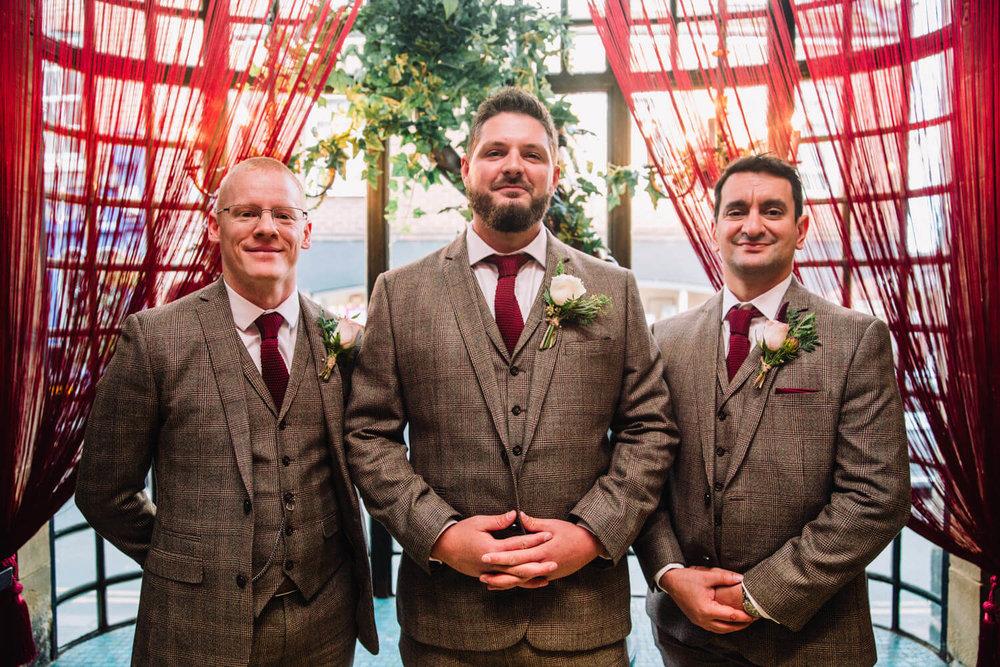 groomsmen portrait in window of belle epoque