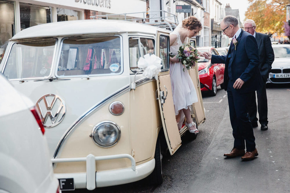 bride stepping out off volkswagon campervan on to King Street in the centre of Knutsford
