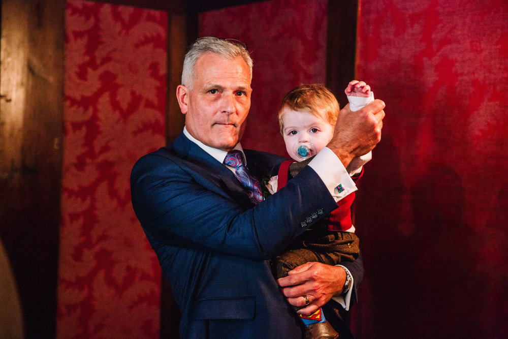father of groom playing with grandson pageboy before ceremony