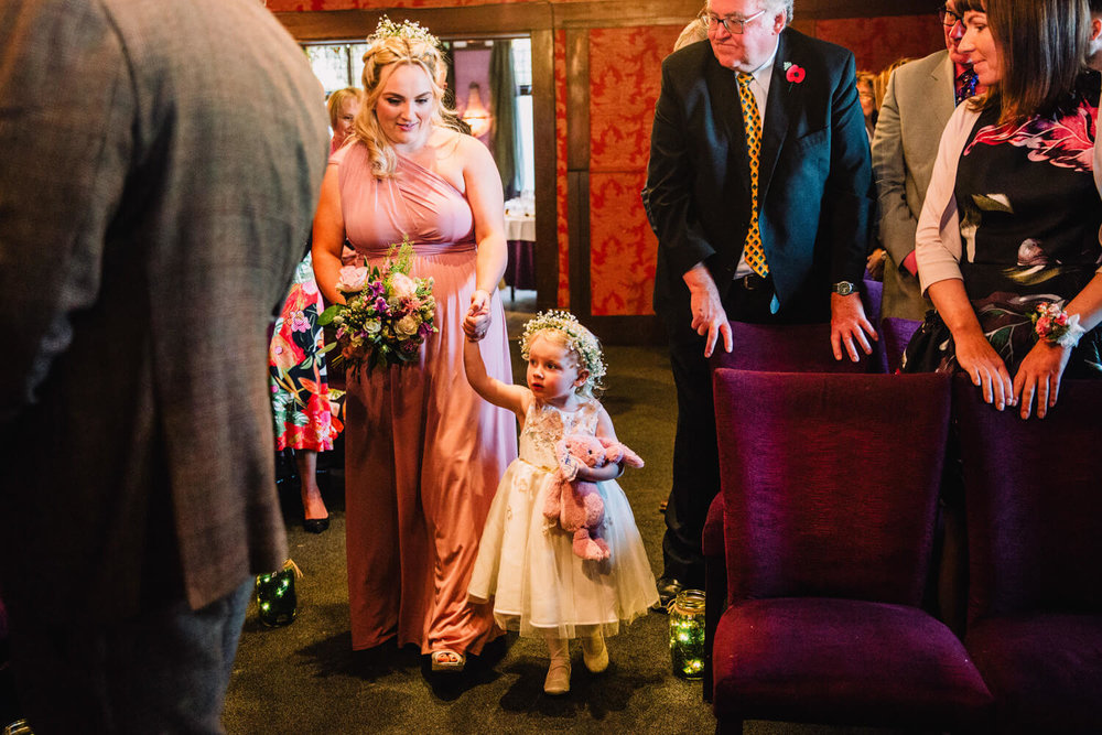 flowergirl walking down aisle with bridesmaid mother
